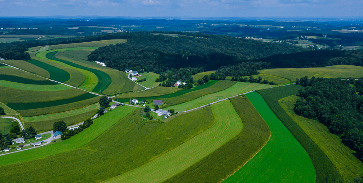 An aerial photo shows green farm land and farm houses in York County, PA.