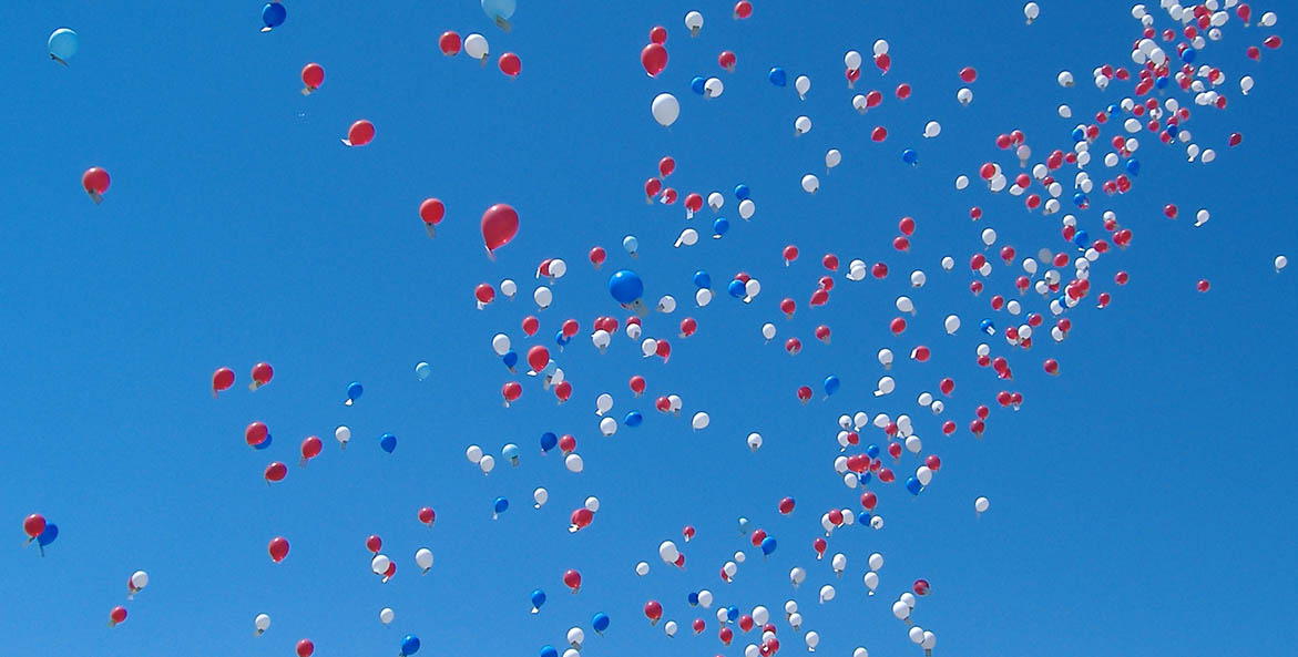 Blue, red, and white balloons rising against a blue sky.