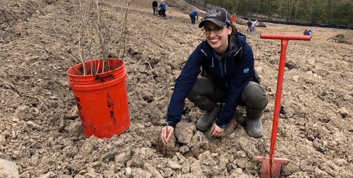 A woman plants saplings in a barren field in Pennsylvania