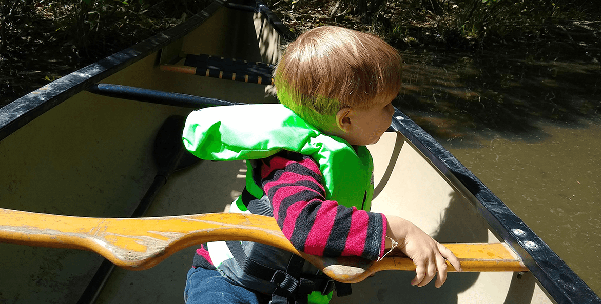 Child on a canoeing trip wearing a life jacket.