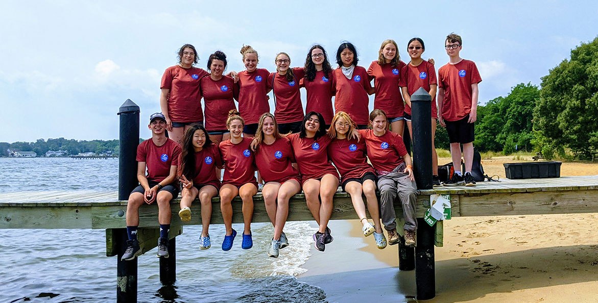 A group of students stand on a dock