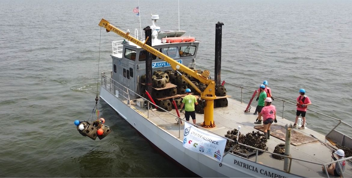 A workboat with large yellow crane lowers a grouping of concrete balls and red, blue, and white buoys. There are people with hardhats standing on the boat.