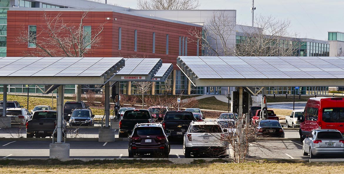 Cars are parked under solar arrays in a school parking lot.
