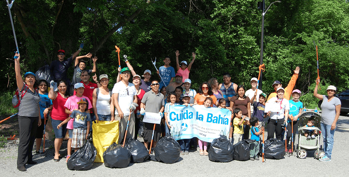 A group poses with a banner after picking up litter