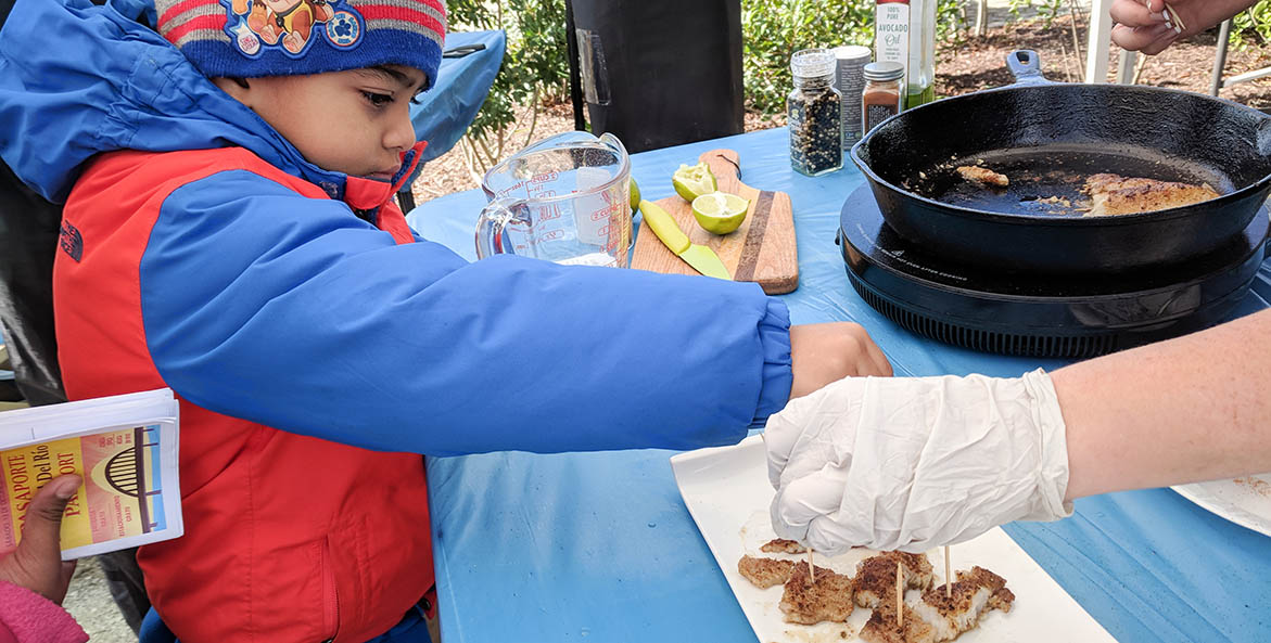 Young boy reaches for prepared fish on a demonstration table.