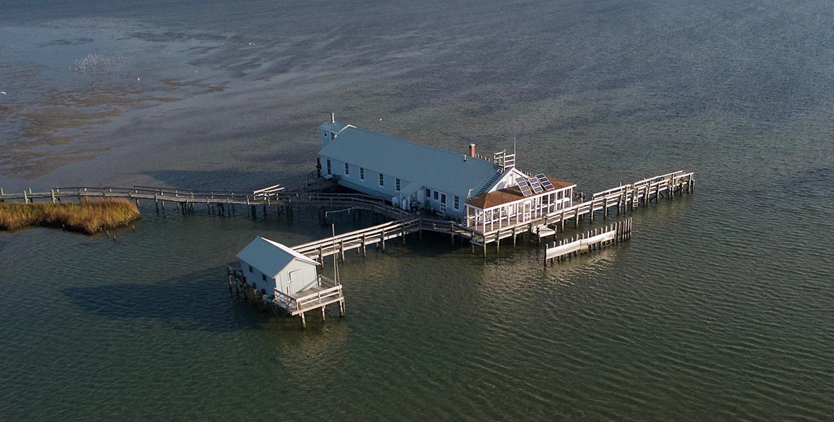 A building on stilts is completely surrounded by water.