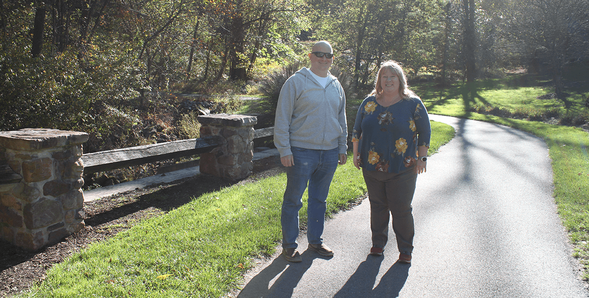 Man and woman stand on paved walking trail in front of grass and trees.