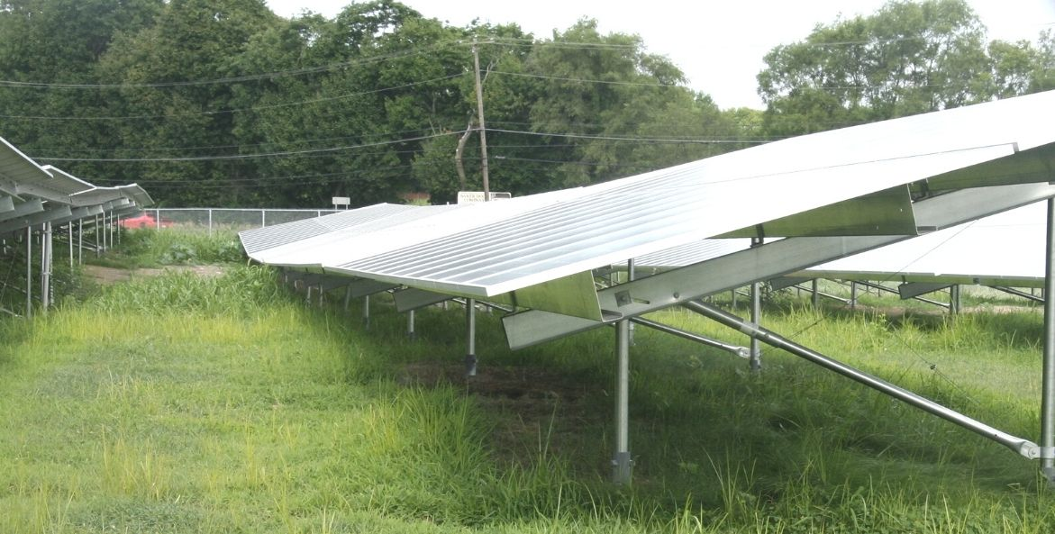 Large solar panels sit in a row on green grass