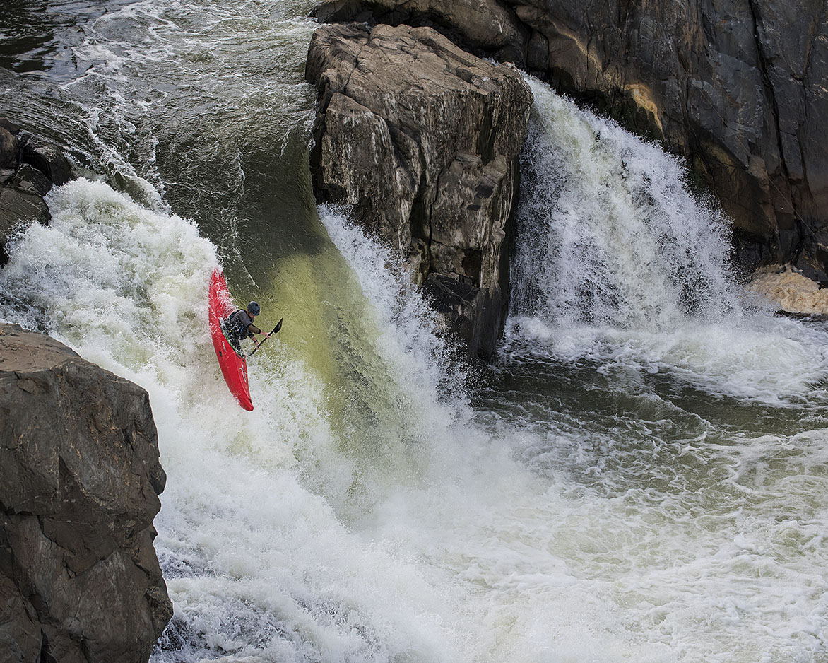 A kayaker in a bright red kayak paddles vertically down whitewater on a waterfall.