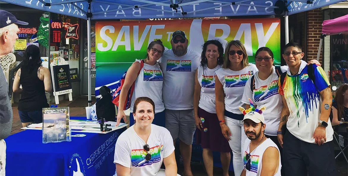Staff members wearing CBF PRIDE t-shirts pose in front of the organization's tent.