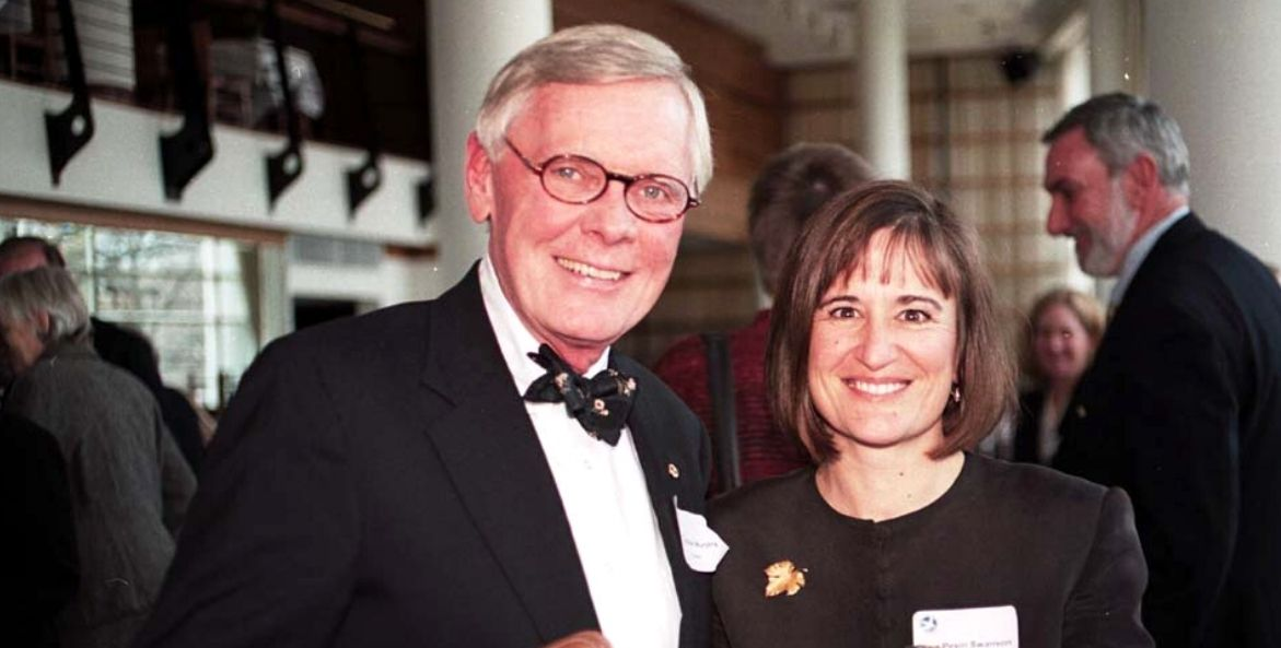 A man with glasses and a tuxedo stands next to a woman in a black jacket. Both people are looking at the camera and smiling.