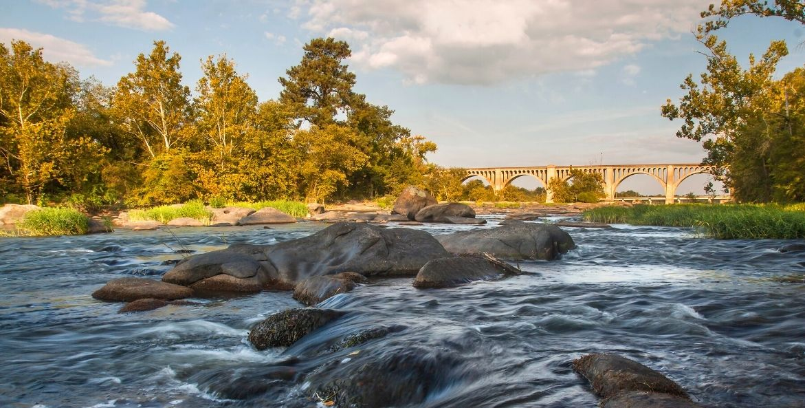 A river rushes over boulders in front of a large bridge