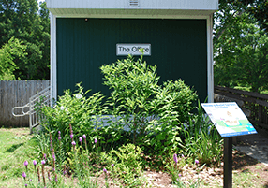 A compact garden with healthy plants stands in front of a small building. An informational plaque stands in front.