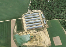 Aerial photo of farmland with six long, narrow buildings.