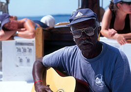 Earl White plays guitar on a pier.