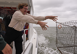 A man throws a wire square cage over the side of a boat as whitewater sprays the air.