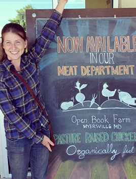 Proprietor of Open Book Farm, MK Barnet, stands in front of a sign adverting her products.