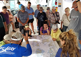 Men and women stand around a table looking at a map of the Chesapeake Bay.