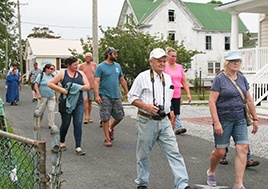 Men and women walk down a road lined with homes.