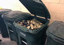 A green trash bin's open top reveals that it is full of oyster and clam shells.
