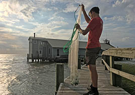 Boy with fishing net in front of Fox Island Lodge in the middle of the Chesapeake Bay.