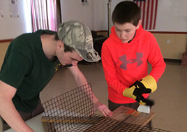 Eagle Scout helps younger Boy Scout assemble an oyster cage.