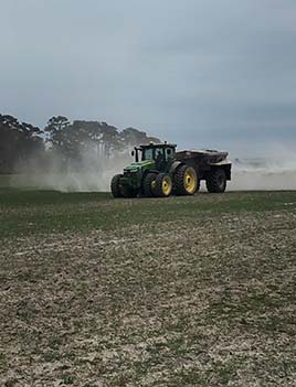 A photo of a tractor spreading fertilizer.