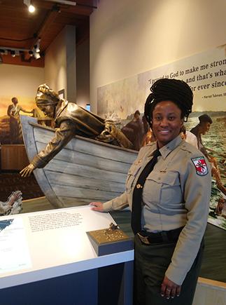 Woman park ranger stands next to museum exhibit