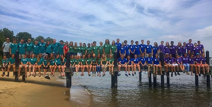 Large group of students posing for photo on pier extending over water.