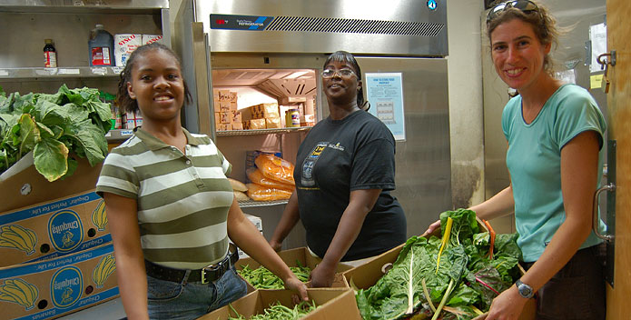 Three volunteers hold boxes of fresh green beans and greens.