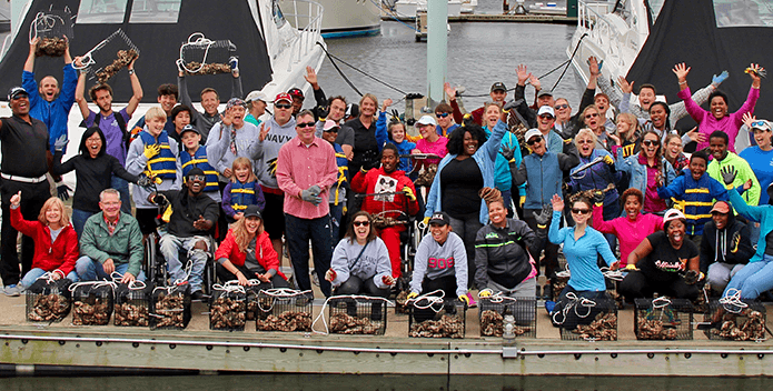 Dozens of residents wave and display their oyster gardening cages on a pier in Baltimore.