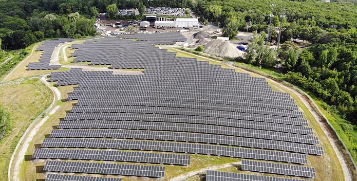 Rows of solar panels fill a 12-acre field.