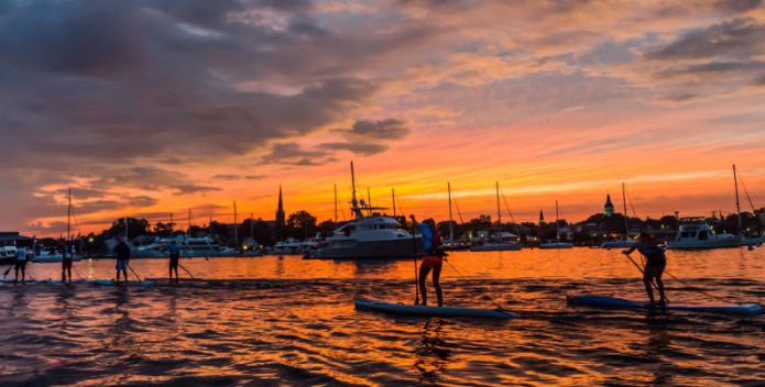 Image of a paddleboarders in the late summer sunset.
