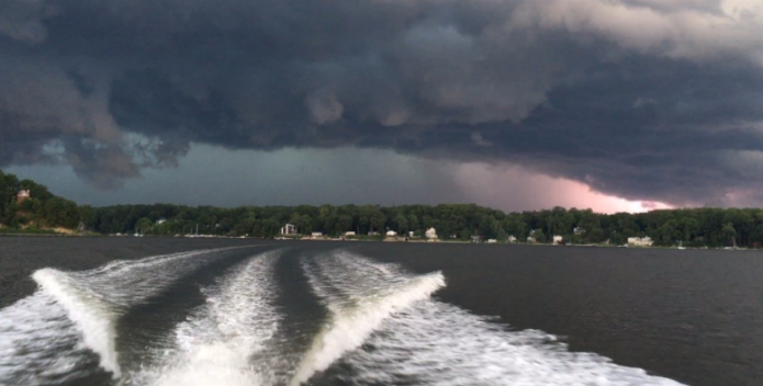 Image of a boat outrunning an approaching storm.