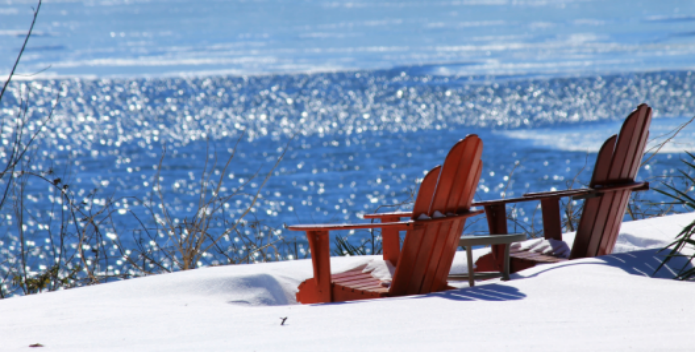 Image of two adirondack chairs on a blanket of snow on the ground.