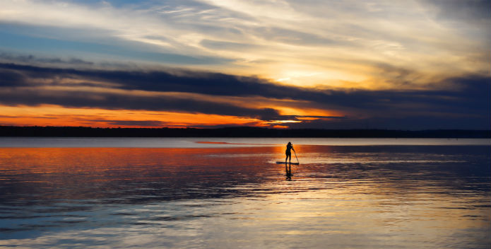 Image of a stand-up paddleboarder in the sunset.