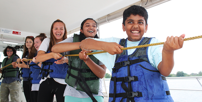 Students aboard a boat are all smiles while they pull in a rope.