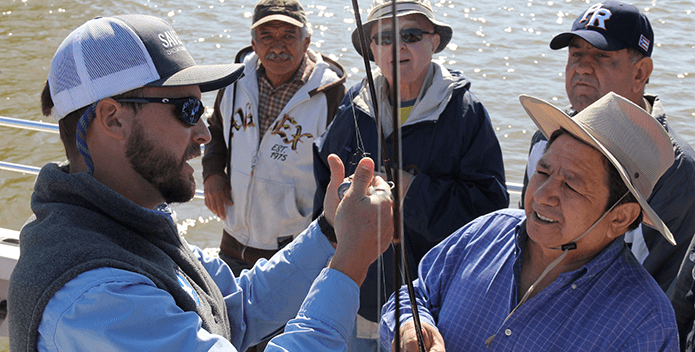 CBF Educator Rick Mittler rigs rods on a fishing trip with Richmond, Virginia Hispanic leaders.