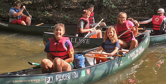 smiling students in canoes SWEEP 695x352