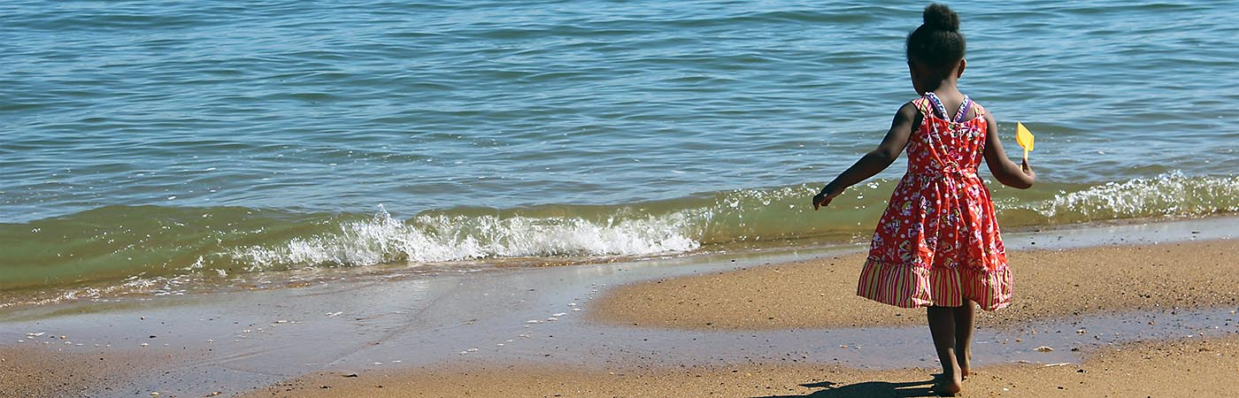 A little girl tentatively dips her toes into a pool of water along the sandy beach of the Bay.