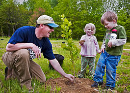 Father and children plant a tree at Holly Beach Farm.