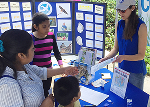 Photo of a CBF volunteer speaking with a woman and her children at CBF's festival booth.