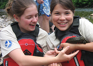 Photo of two female students holding a hellbender salamander