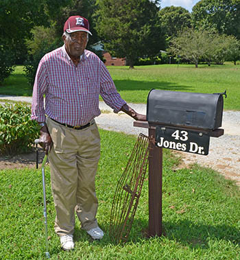A man standing next to his mailbox in front of his house with oyster tongs nearby.