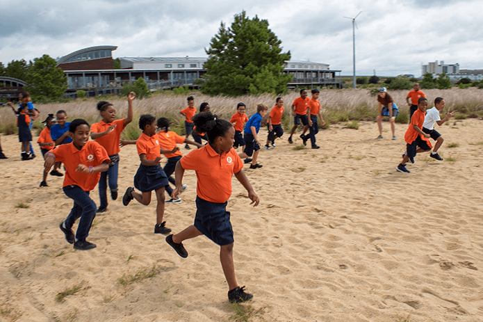 Black youngsters dash across the sandy beach of CBF's Brock Environmental Center.