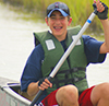A smiling student canoeing during a CBF field experience. Photo by CBF Staff.