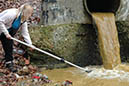 A woman works to clean up polluted runoff running into her local stream.