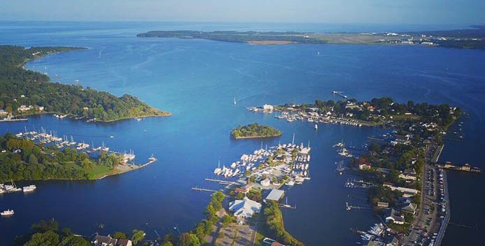 Aerial photo of Solomons Island. The photo looks over the bule of the Bay and the green of the island.