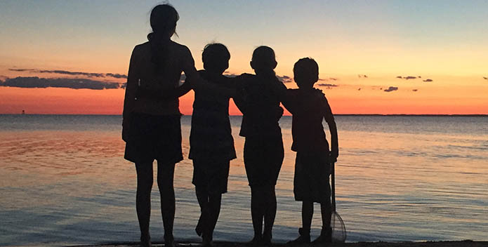 Silhouette of four children at the waters edge, backlit by a sunset.