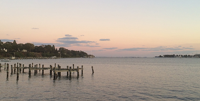 Photo of the Chesapeake Bay with an aging dock in the foreground and a rosy sunset in the background.
